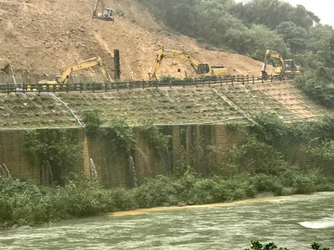 目前邊坡逐漸穩定,正在施打第二階鋼軌樁,並使用1台抽水機將工區多餘積水排除。(陳彩玲攝)