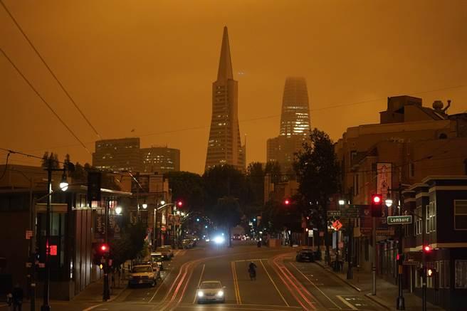 今年9月9日,美國加州舊金山哥倫布大道的一景。嚴重的山林大火,造成的濃煙微粒遮蔽了陽光,變成橙色的天空。嚴重的空汙造成五個州520萬人的呼吸道疾病。(圖/美聯社)