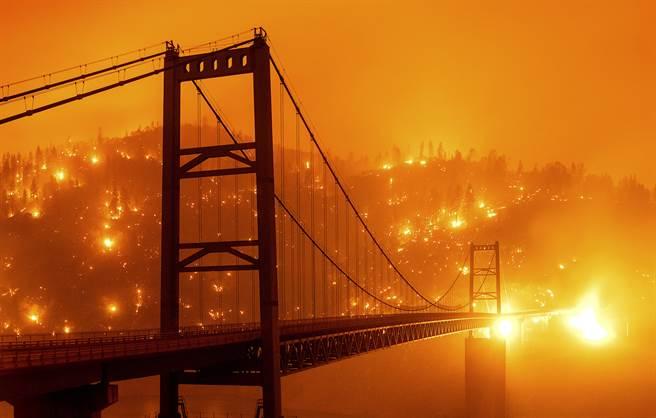 奧羅維亞的比得韋爾吧大橋,這是一座山區的吊橋,隔著河流看到對面的山林大火。(圖/美聯社)