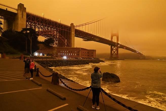 舊金山地標金門大橋的一景,受到嚴重山林大火影響,天空都呈現橘黃色,這是大量的浮游粒子吸收了陽光中的藍光所致,所黃昏晚霞的原理相同。(圖/美聯社)