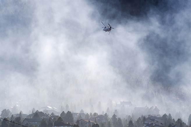 消防員試著以直升機載水來滅火。(圖/美聯社)