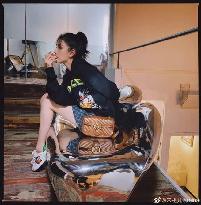 宋祖兒穿上全套 Gucci 黑色復古帽T搭配上藍色印花短裙,腳踩低筒白球鞋,大秀纖細的長腿。(圖/摘自微博@宋祖儿lareina)