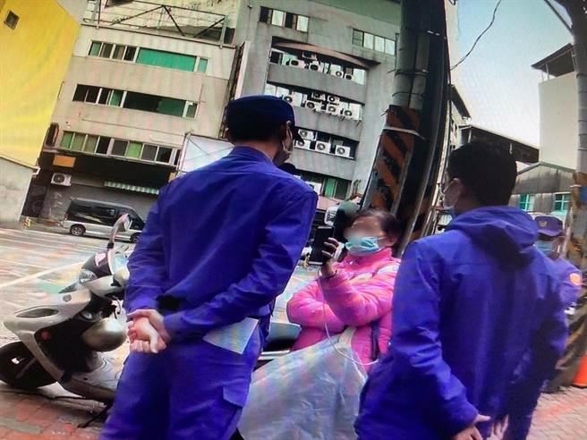 台南市警方派員到場戒護,不讓蘇大媽(著紅衣)阻撓事務官的執行。(讀者提供/洪榮志台南傳真)