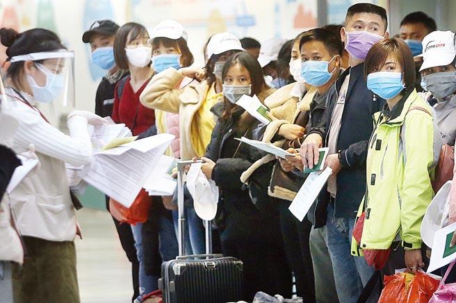 中央流行疫情指揮中心擬加強移工檢疫措施,針對後7天的自主健康管理,將由專人進行追蹤。圖為在桃園機場入境管制區內,一群越籍移工準備通關入境。(本報資料照片)
