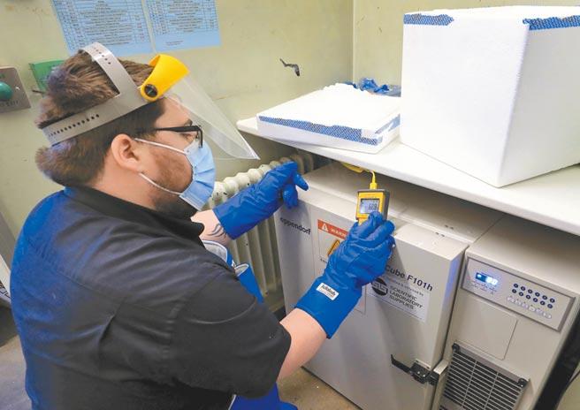 在英國英格蘭,一名藥局技術人員正準備儲存第一批輝瑞疫苗,預定從今天起開始施打。(美聯社)