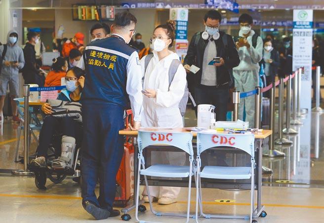 台灣自12月1日起實施「秋冬專案」加強防疫。圖為桃園機場旅客下機後,檢疫協勤人員核示入境檢疫聲明書。(本報系資料照片)
