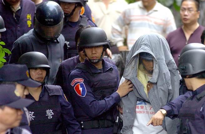 警方逮捕涉嫌槍殺橫科所員警的兄弟檔嫌犯,哥哥王柏忠(右二頭套衣服者)與弟弟王柏英(左二戴安全帽者)在警力戒護下押解上車。(中時資料照 季志翔攝)