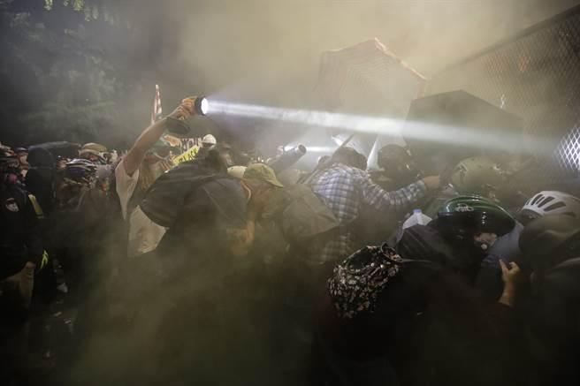 在波特蘭,抗議「黑人的命也是命」的群眾不畏懼警方祭出的催淚瓦斯,蜂擁衝向拒馬並試圖推倒。