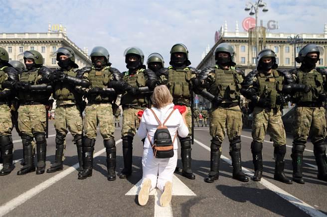 在名斯克8月的遊行中,1名婦女曲膝跪在全副武裝、手牽著手排成緊密隊形的鎮暴警察前。在強勢的警力下,女孩顯得這麼弱小無助,就像她們的訴求一樣的卑微。