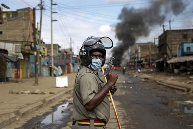 肯亞警方允許使用催淚瓦斯來貫徹封鎖令,導致過度執法與侵害人權的事件時有所聞。圖為警方持槍向焚燒輪胎表達抗議的民眾示威;但對於只是想有一口飯可吃,且手無寸鐵的民眾掏槍,難免讓人質疑「殺雞焉用牛刀」。