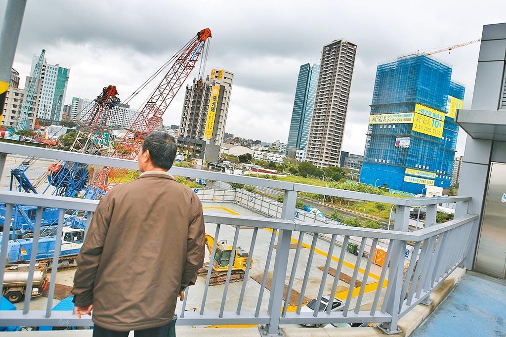 圖為民眾路過新北市新莊區興建中建案,佇足觀看。(杜宜諳攝)