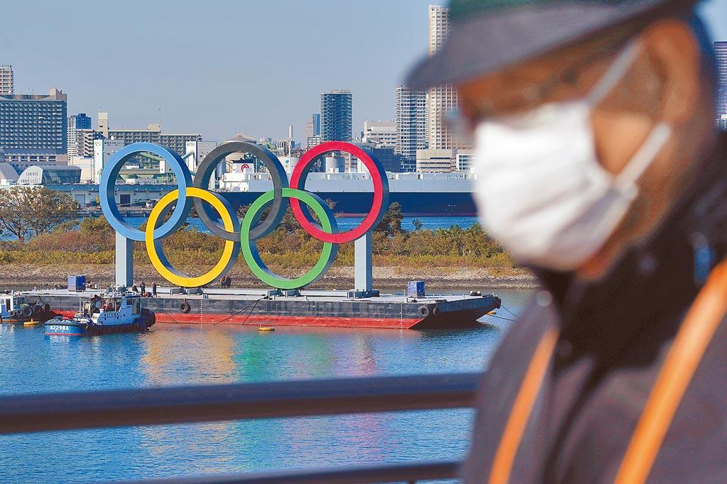 一名戴口罩的男子在奧運五環背景中行走。(美聯社)