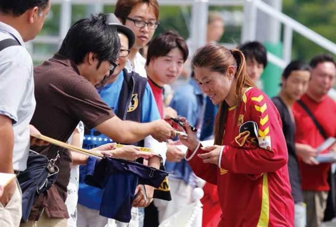 二○一三年效力神戶雌獅的日本球星澤穗希在訓練場替球迷簽名。(圖/商周出版提供)