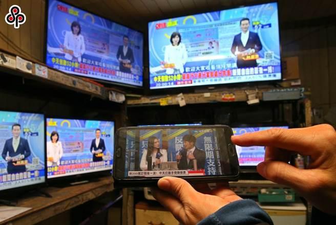 民眾在卖场收看中天新闻,并用手机加入YT频道订阅,表达支持之意。(本报资料照)
