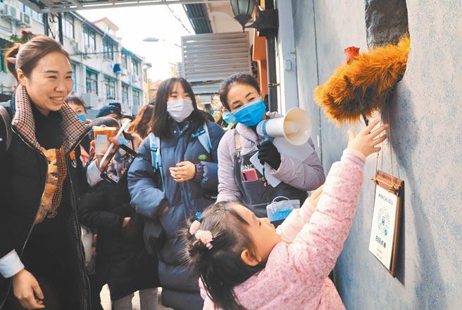 12月6日,民眾排隊購買「熊爪」咖啡,一名小孩與店員透過洞口互動。(中新社)