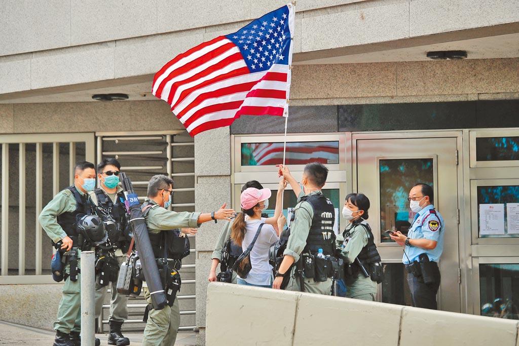 大陸外交部昨天宣布取消美國外交官赴港不需申請簽證措施。圖為今年7月4日港人手持美國國旗在美國香港領事館前遭到鎮暴警察包圍。(美聯社)