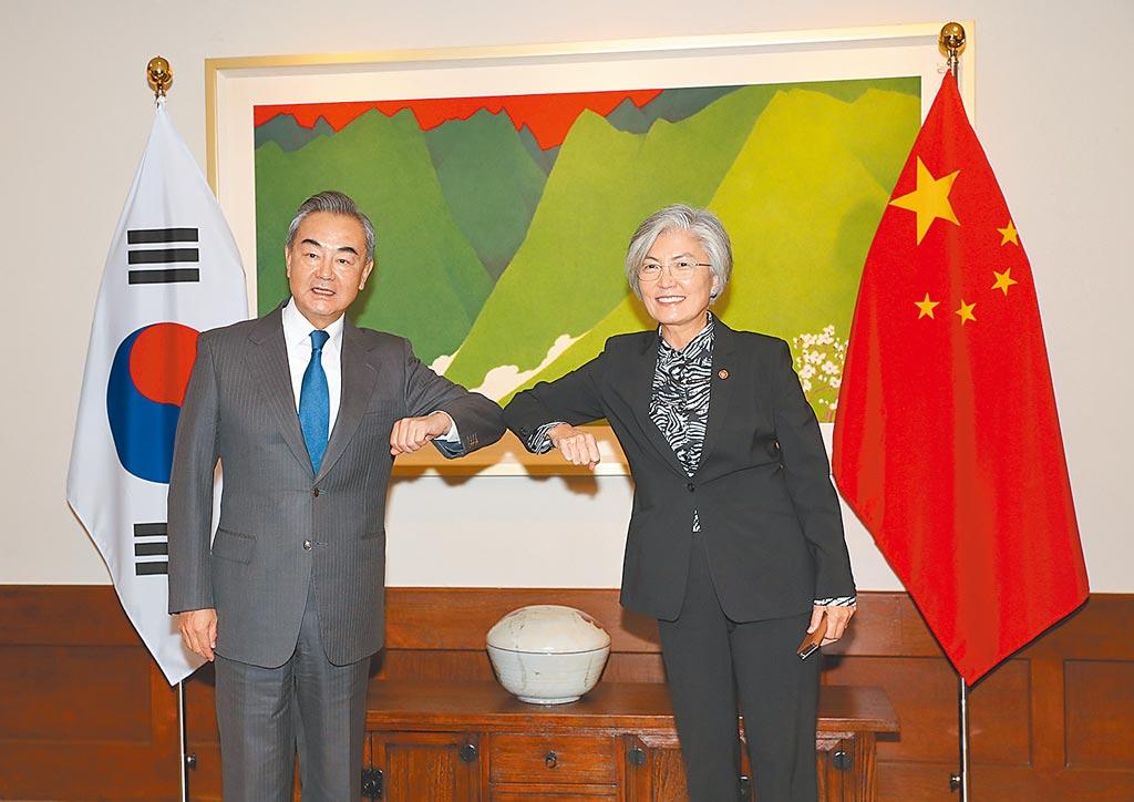 大陸外長王毅(左)11月連訪日韓,圖為11月26日,王毅在首爾同韓國外長康京和舉行會談後碰肘致意。(新華社)