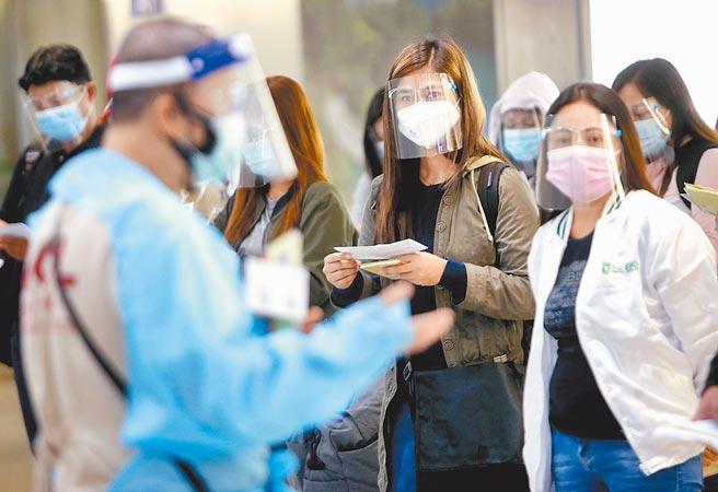 台北市長柯文哲意有所指表示,台灣有感染,每個人都倒楣。圖為桃園機場入境管制區內,一群剛下機的菲籍移工,在勞動部人員引導下準備通關入境。(范揚光攝)
