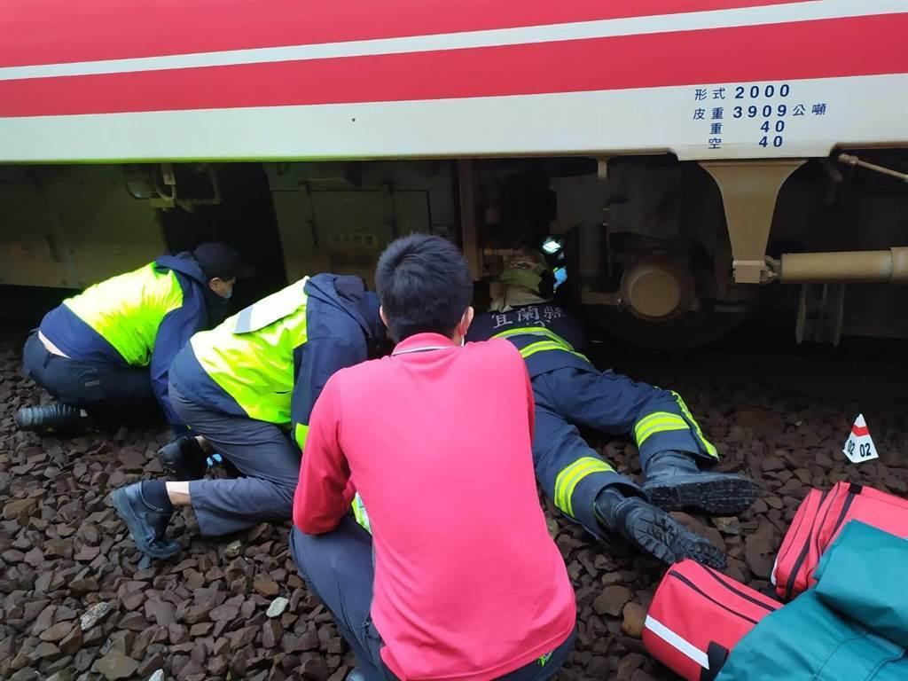 救難人員將卡在列車下的婦人救出後緊急送醫救治。(宜蘭縣政府消防局提供/ 胡健森宜蘭傳真)