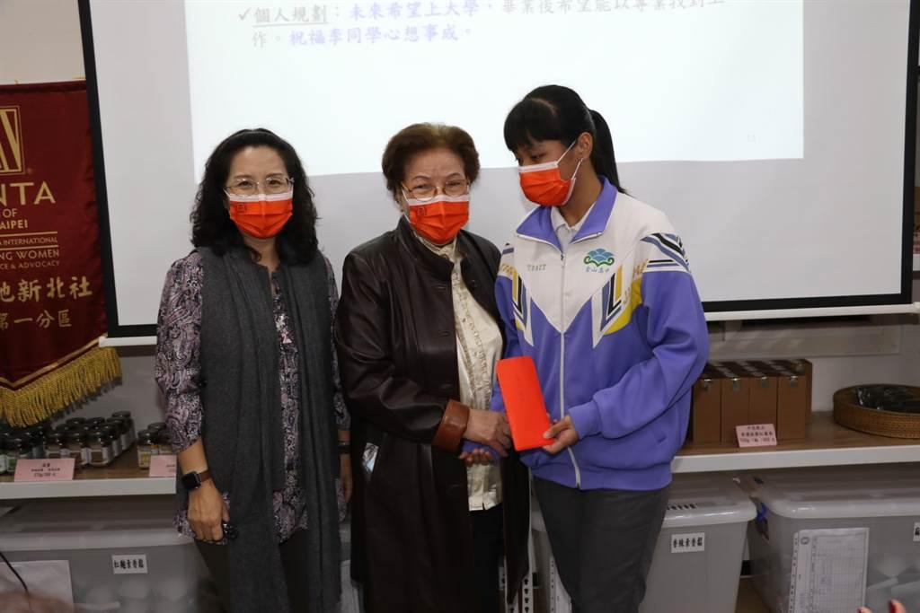 國際崇她社新北社獎學金委員長李子美(中)捐贈5千元給金山高中新住民同學。(新北市社會局提供)