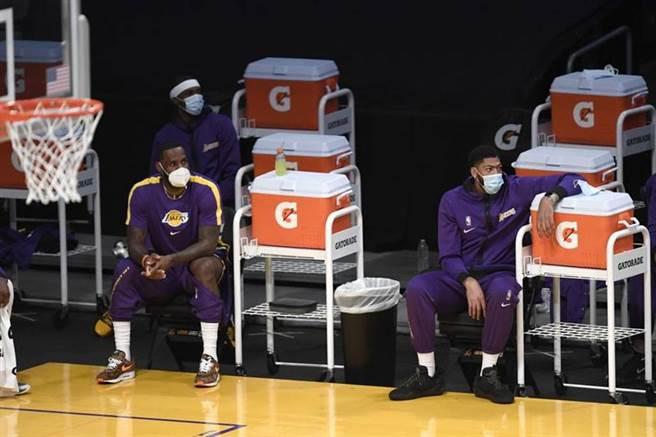 湖人球星詹姆斯(左)、戴维斯坐在场边看比赛。他们两人将成为队史总薪资最高的前5名。(美联社)