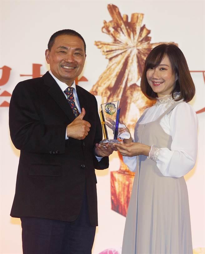 新北市長侯友宜(左)12日在第41屆旺旺‧時報文學獎頒獎典禮,將散文組佳作頒給作家黃庭鈺(右)。(張鎧乙攝)
