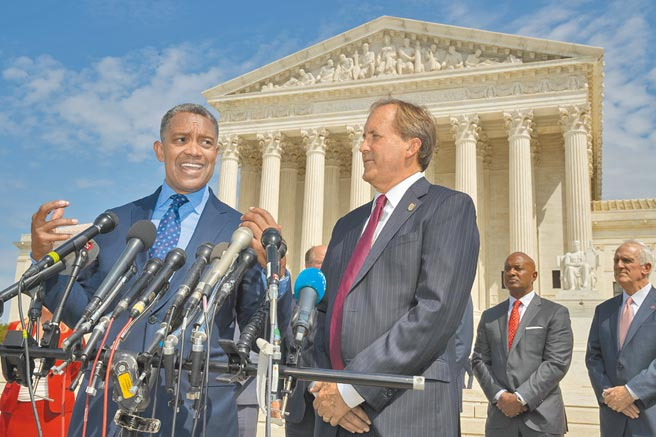 共和党籍的德州州检察长派克斯顿(右),日前向最高法院提讼,要求推翻乔治亚等4州确认拜登胜选的结果。图为派克斯顿去年与一群跨党派州检察长召开记者会。(美联社)