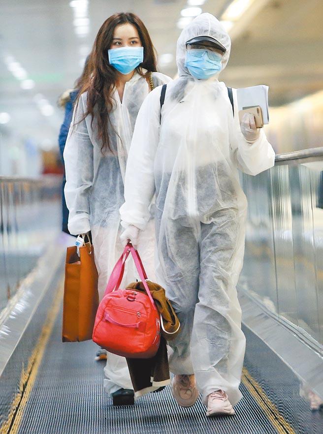 中央流行疫情指挥中心11日公布国内新增1例境外移入新冠肺炎确定病例,在桃园机场入境管制区内,2名身穿防护衣的旅客正准备通关入境。(范扬光摄)