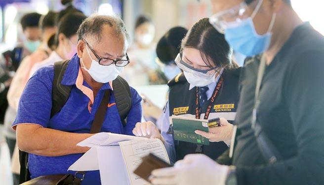 中央流行疫情指揮中心11日公布國內新增1例境外移入新冠肺炎確定病例,在桃園機場入境管制區內,1名防疫人員(中)正協助旅客上網填寫防疫資料。(范揚光攝)