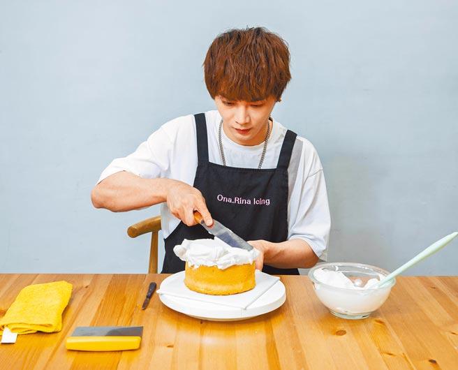 古曜威將奶油抹上蛋糕表面。(石智中攝)