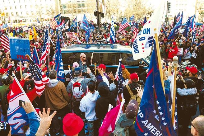 美國總統川普的支持者12日在華府參加遊行時,包圍了一輛汽車,他們誤以為川普坐在車內。(路透)