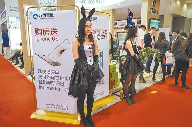 全球資金氾濫推升房地產價格,圖為北京房展會上展商找來模特兒助陣。(中新社資料照片)