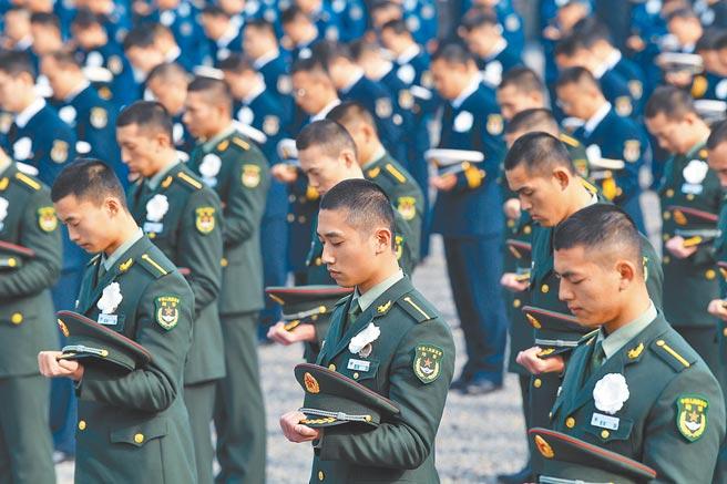 12月13日,解放軍軍人脫帽為遇難者致哀。(新華社)