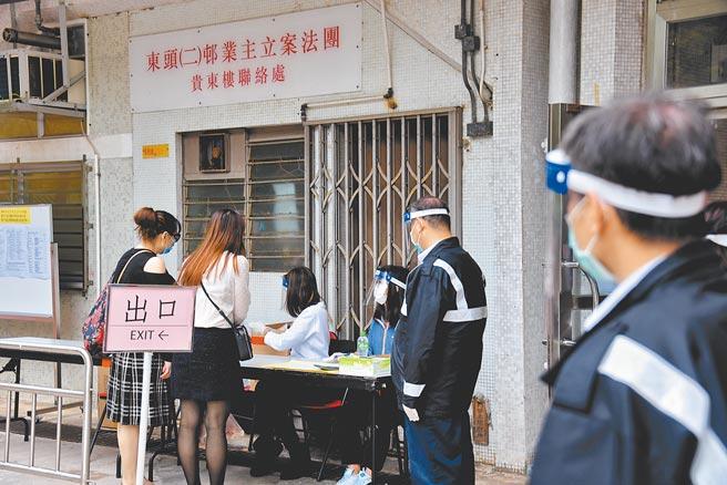 12月13日,香港衛生防護中心向確診者居住社區的居民派發病毒檢測樣本瓶。(中新社)
