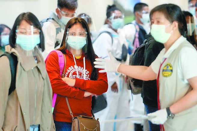 國內新增4例境外移入新冠肺炎確診病例,菲律賓籍與印尼籍各占2例,圖為桃機內剛下機的菲律賓籍移工,在勞動部人員引導下通關入境。(范揚光攝)