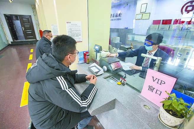 大陸嚴控銀行房貸;圖為2月20日,山西一銀行內民眾在辦理業務。(中新社)