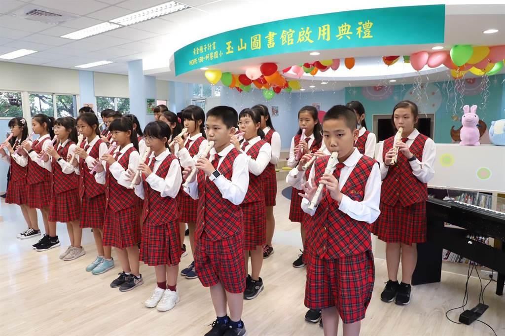 蚵寮國小學童以直笛吹奏悠揚動聽的樂曲,歡喜迎接第158所玉山圖書館啟用。(玉山提供)