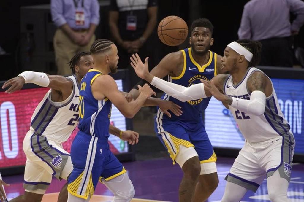 勇士隊Stephen Curry(左)傳球給隊友Kevon Looney。(美聯社)