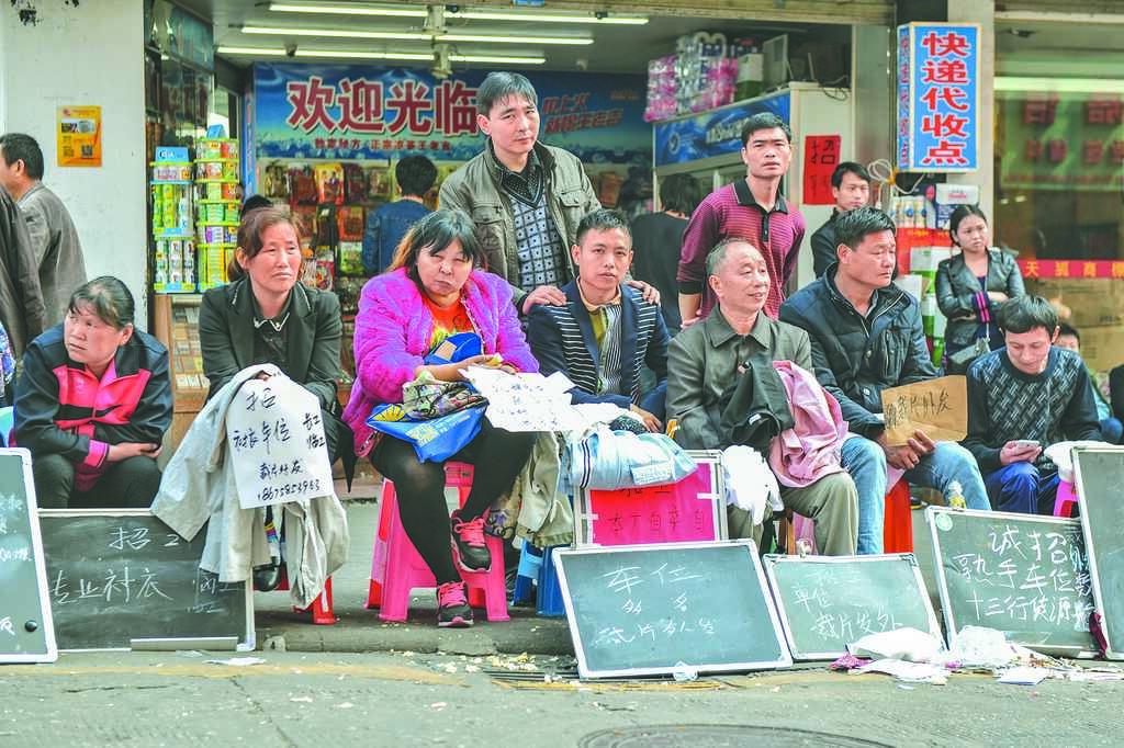 大陸勞動力恐不足,圖為廣州春節過後缺工,製衣廠老闆們直接坐在路邊招工。(中新社資料照片)