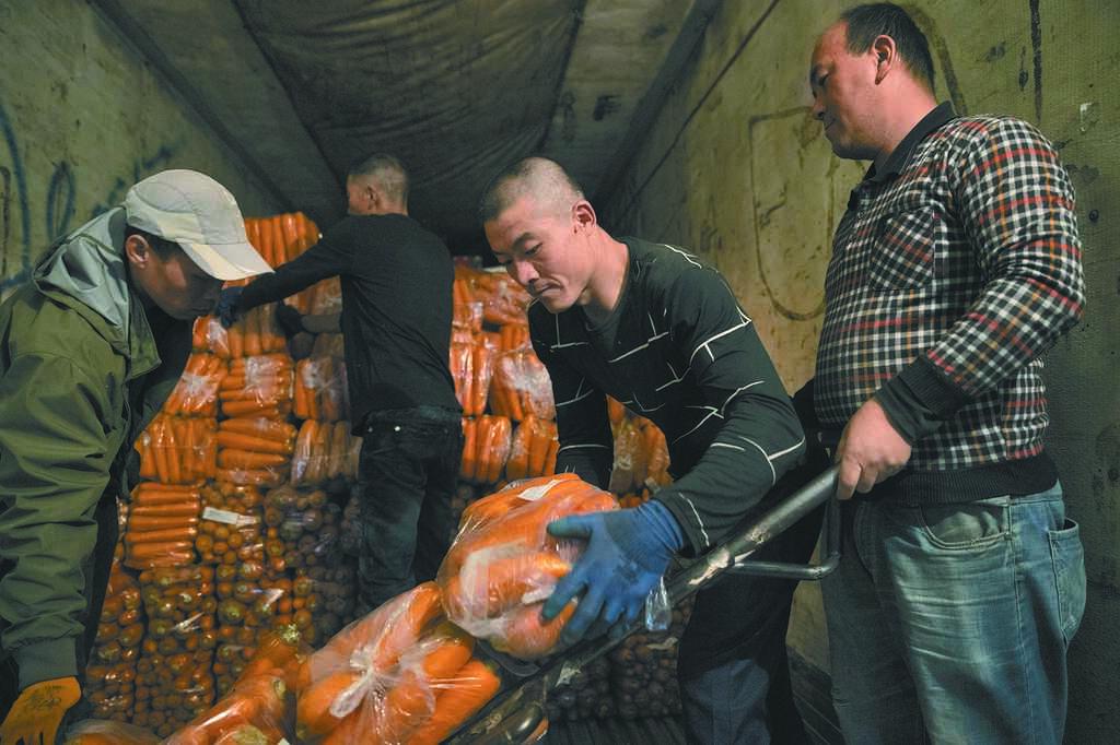 據統計,黑龍江的「打工人」平均年齡超過40歲。圖為10月12日,在黑龍江省綏芬河一公司倉庫內,工人在搬運準備出口的果蔬。(新華社)