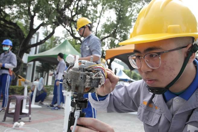 学生细心将电扇一一拆解,进行灰尘清除及上油等工作。(吴建辉摄)