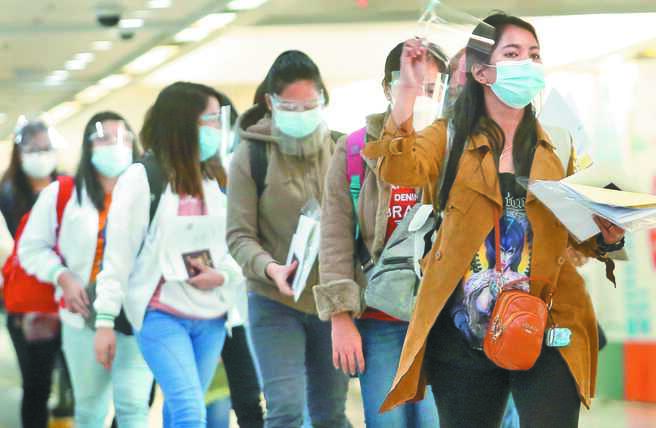 國內新增2例境外移入新冠肺炎確定病例,其中菲律賓籍與印尼籍各佔1例,圖為桃機剛下機的菲律賓籍移工,在勞動部人員引導下準備入境。(范揚光攝)