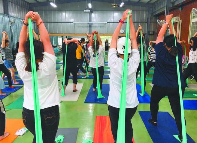 台中市辦理體能運動工作坊,讓照顧服務員學習正確運動,緩和肌肉緊繃並提升肌力。圖為彈力帶運動。(弘道基金會提供/陳世宗台中傳真)