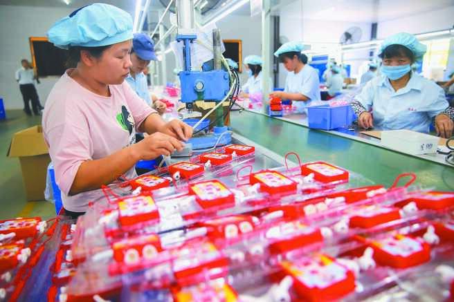 今年大陸全面建成小康社會。圖為廣東一「扶貧車間」玩具廠,工人在流水線工作。(中新社)