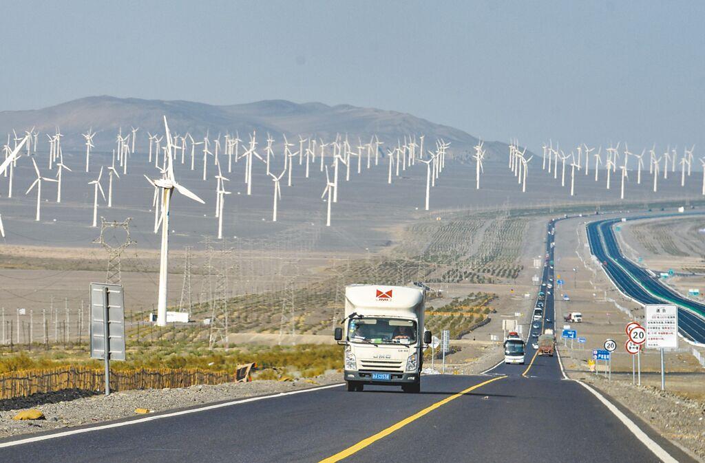 汽车行驶在新疆吐鲁番市郊区风力发电场一旁的公路上。(新华社资料照片)