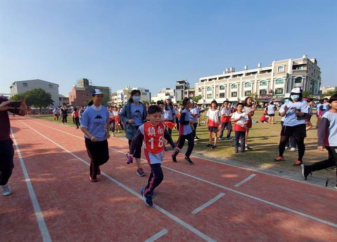 镇南国小五年级小朋友林洧聪接棒后摇摇晃晃奋力往前,班导王幸芙和助理员陪跑,班上同学跟着慢跑加油。(周丽兰摄)