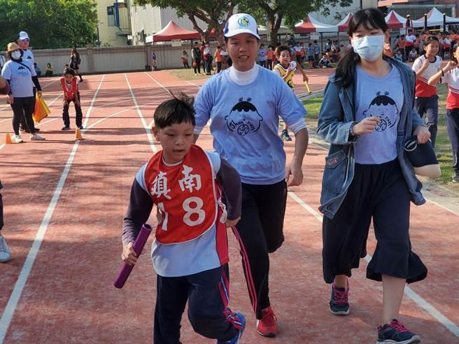 林洧聪小朋友在全班同学帮助下,完成人生第一次大队接力。(周丽兰摄)
