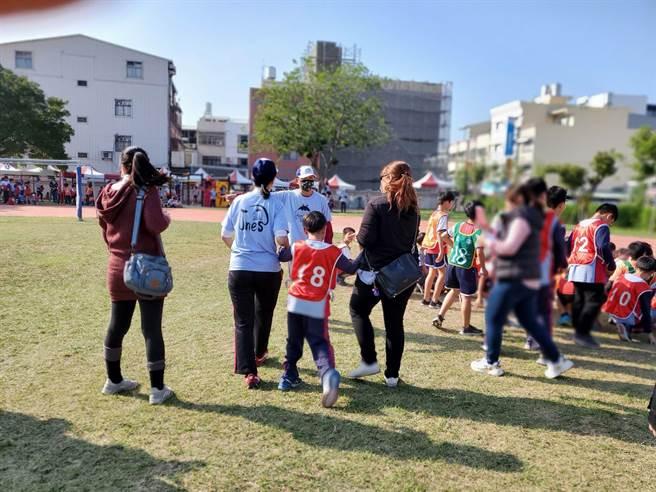 林洧聪小朋友赛前由妈妈(右)、学校助理员陪伴。(周丽兰摄)