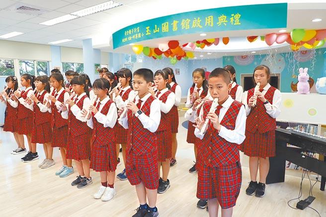 蚵寮国小学童以直笛吹奏悠扬动听的乐曲,欢喜迎接第158所玉山图书馆启用。图/玉山银行提供