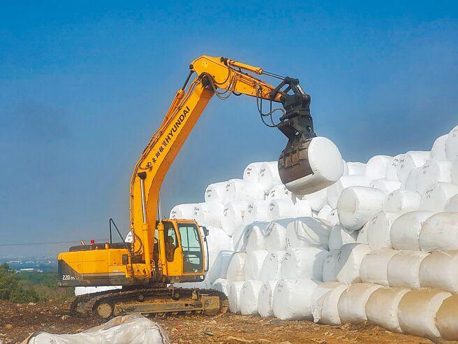 打包好的垃圾每個重約1公噸,怪手夾起排成金字塔形狀。(周麗蘭攝)
